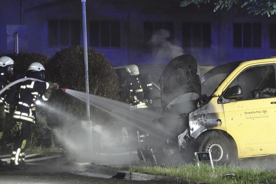 Die Kameraden der Feuerwehr löschen die Flammen an einem der Postfahrzeuge. Zwei Transportwagen brannten komplett aus, ein dritter wurde stark beschädigt.