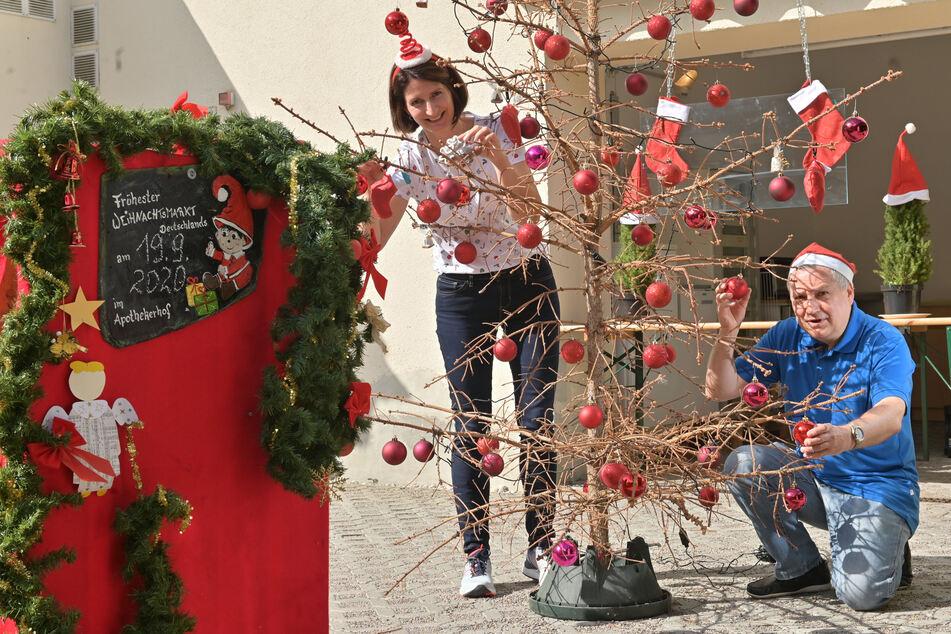 Dorit Türpe (44) und Jürgen Hoffmann (60) schmücken den Tannenbaum vom vergangenen Jahr für den Satire-Weihnachtsmarkt.