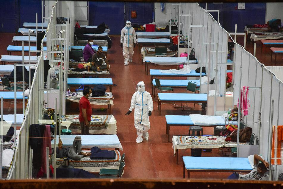 Medizinische Mitarbeiter in Schutzkleidung behandeln Covid-19-Patienten in der Quarantänestation eines provisorischen Krankenhauses in einer Sporthalle in Neu-Delhi. (Symbolbild)