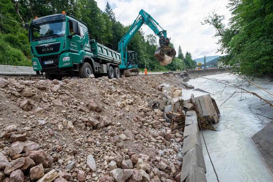 Wie hier auf der Bundesstraße 20, kurz vor Berchtesgaden, laufen die Aufräumarbeiten nach dem Hochwasser-Chaos in Deutschland auf Hochtouren.