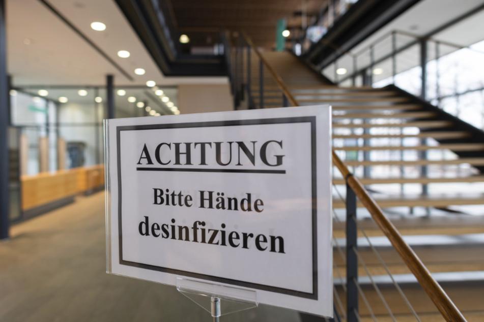 """Ein Schild """"Achtung Bitte Hände desinfizieren"""" steht vor Beginn einer Sondersitzung des Landtagspräsidiums im Sächsischen Landtag im Foyer."""
