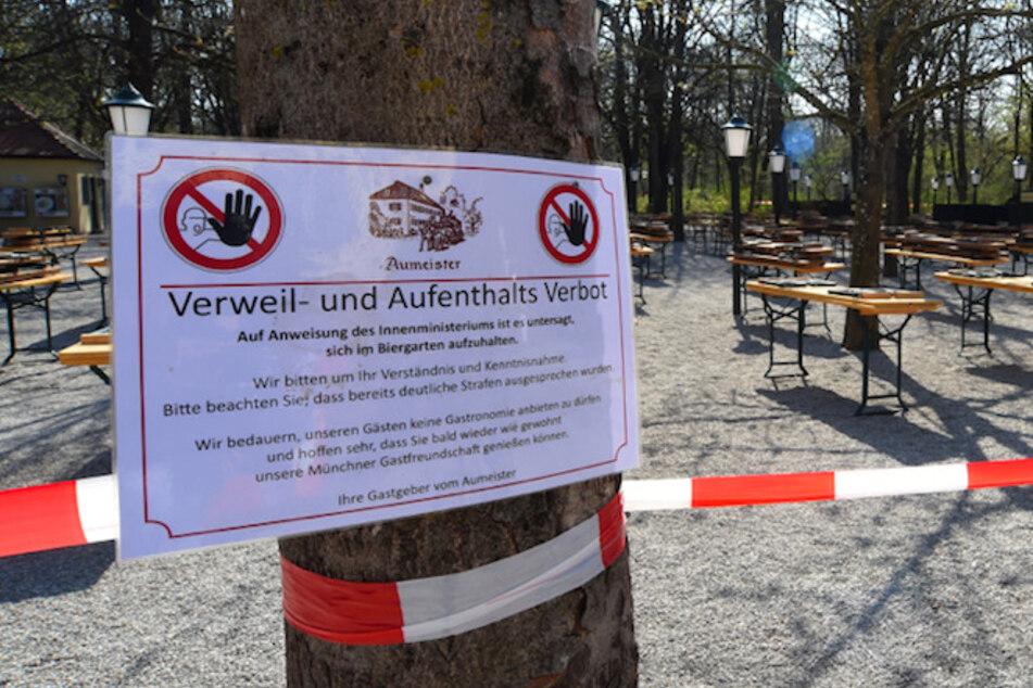"""Ein Schild mit der Aufschrift """"Verweil- und Aufenthalts Verbot"""" hängt an einem Baum am Biergarten am Aumeister im Englischen Garten."""