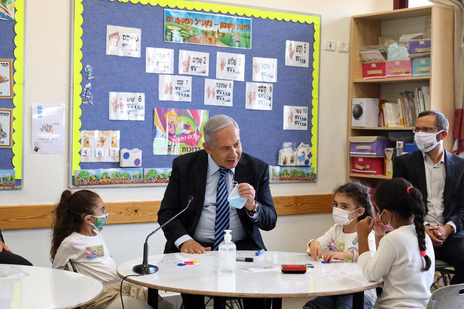 Benjamin Netanjahu (M), Ministerpräsident von Israel, und Bildungsminister Yoav Galant (r) sprechen mit Schülern während ihres Besuchs an der Netaim-Schule zu Beginn des Schuljahres 2020-2021 während der Corona-Pandemie.