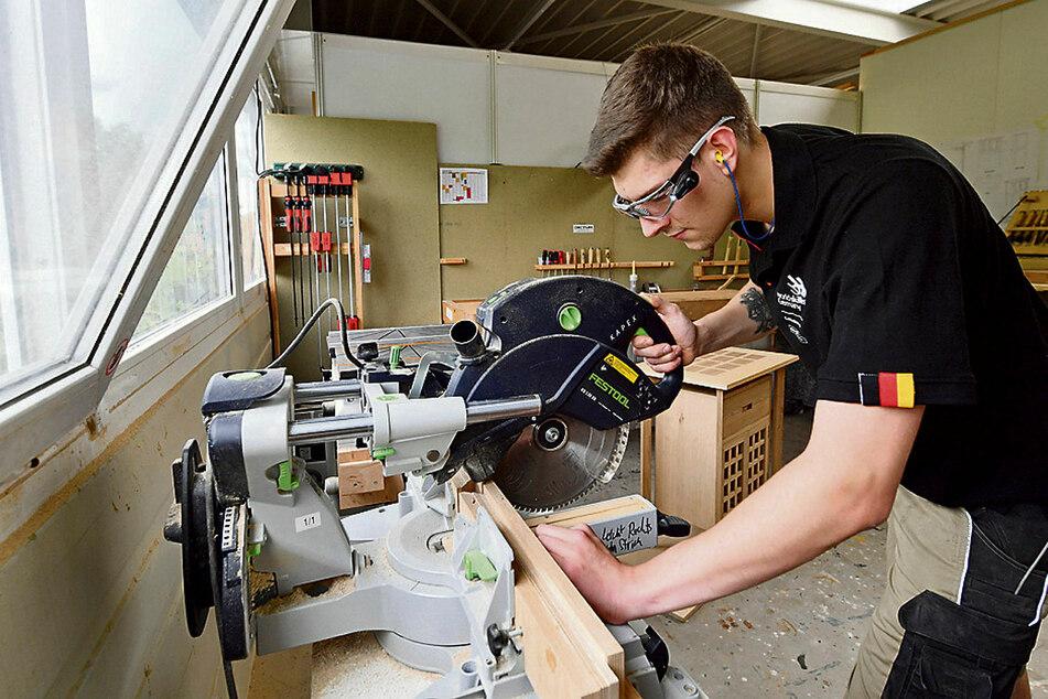 Ein Tischler beim Zuschneiden einer Holzleiste - dieses Handwerk gehört zu den begehrtesten Ausbildungsberufen.