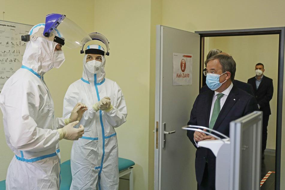 Armin Laschet, NRWs Ministerpräsident (r, CDU), spricht im Gesundheitsamt Köln mit Mitarbeitern in einem Testraum für Abstriche.