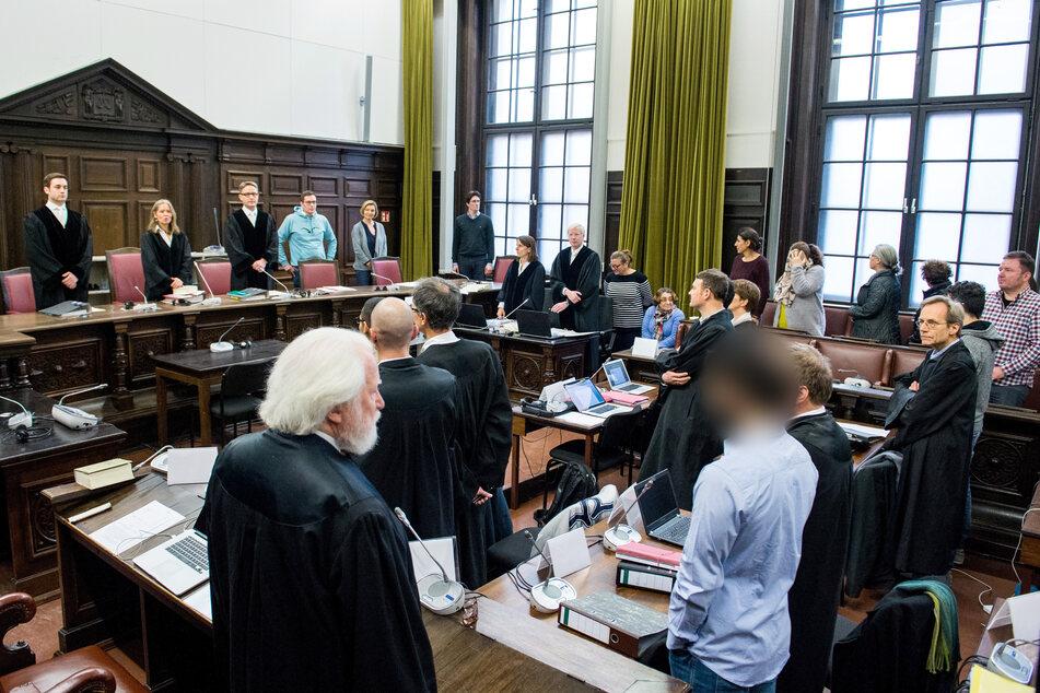 Die Angeklagten stehen mit ihren Anwälten im Landgericht im Saal.