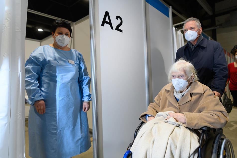 Die 93-jährige Felizitas Diestel aus Dresden wird im Impfzentrum in der Sachsen Arena in Riesa im Rollstuhl zum Impfen gegen Corona geschoben.