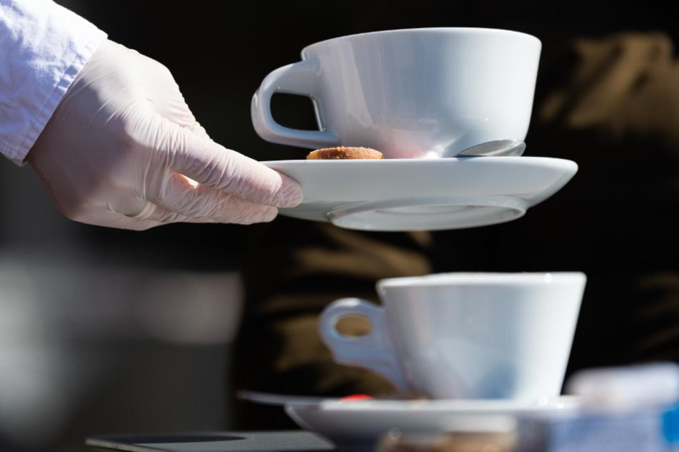 Dresden: Mit Gummihandschuhen wird in einem italienischen Eiscafé draußen serviert.