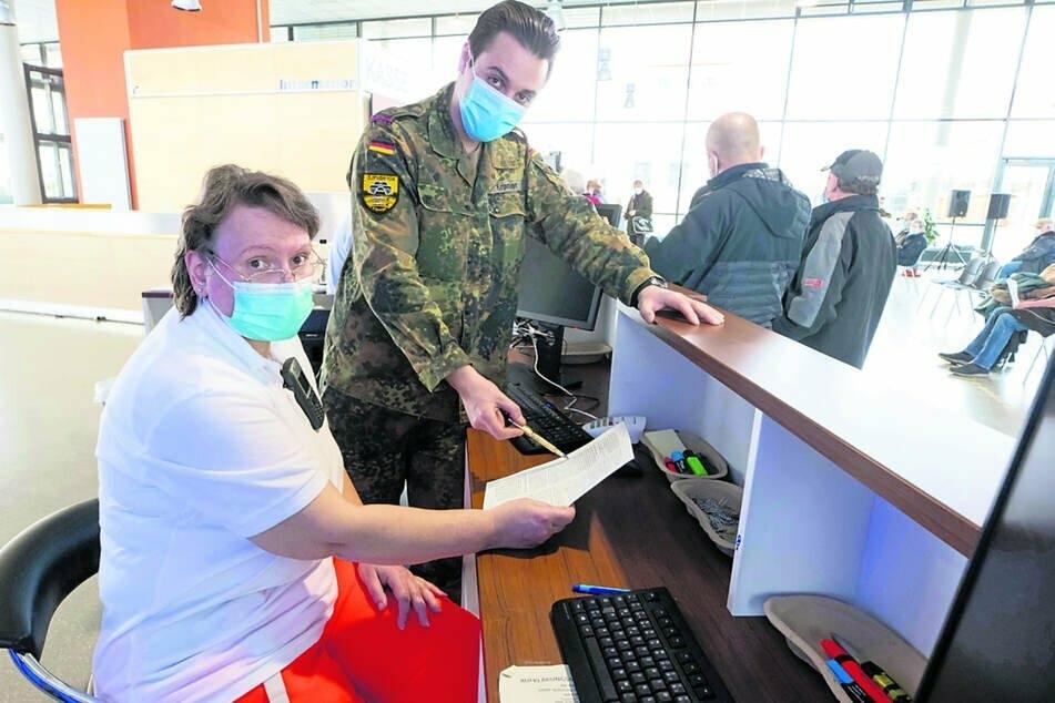 Oberfeldwebel Andrei Kramer (29) beim Schichtwechsel mit einer DRK-Mitarbeiterin.