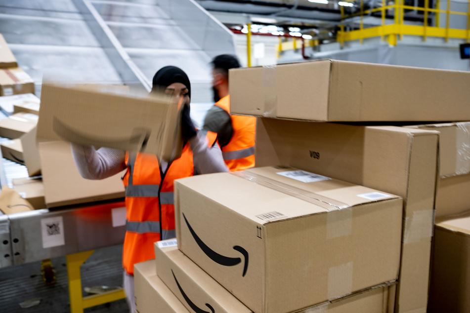 Mitarbeiter des Paketversenders Amazon sortieren Pakete.