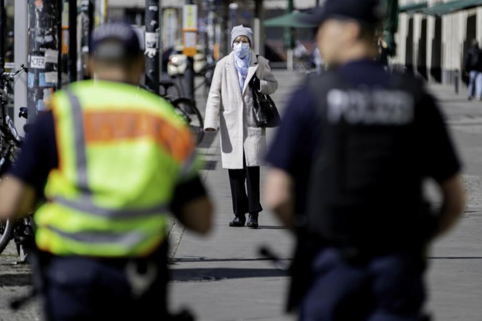 Eine Frau mit Mundschutz kommt am Alexanderplatz zwei Polizeibeamten der Brennpunkt- und Präsenzeinheit (BPE) der Polizei Berlin entgegen.