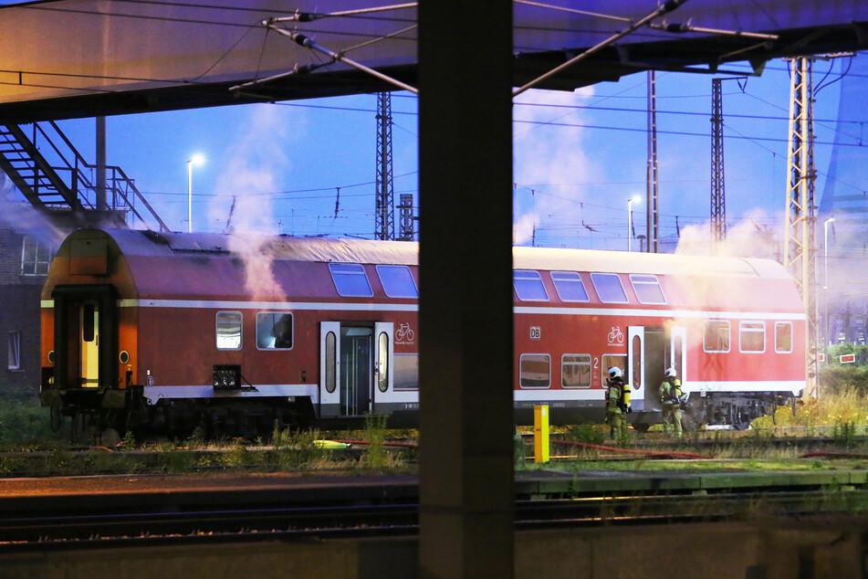 Rauch quillt aus den Fenstern und Türen des lodernden Zugwaggons.