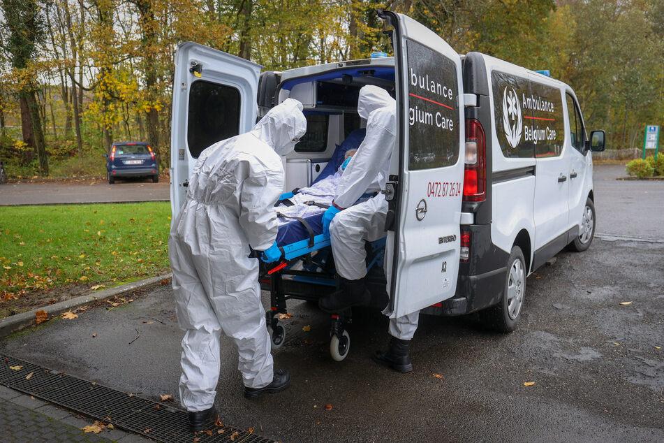 Mitarbeiter transportieren einen Patienten, der von einem Krankenhaus in ein Genesungszentrum gebracht wird.