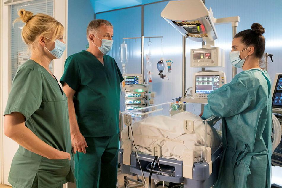 """""""Augen zu und durch"""": Dr. Roland Heilmann (Thomas Rühmann, 65) und Dr. Ina Schulte (Isabell Gerschke, geb. 1979, l.) sprechen mit einer Mutter über ihr schwer krankes Baby."""