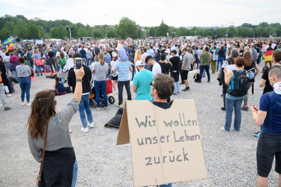 """Ein Mann trägt ein Schild mit der Forderung: """"Wir wollen unser Leben zurück."""""""