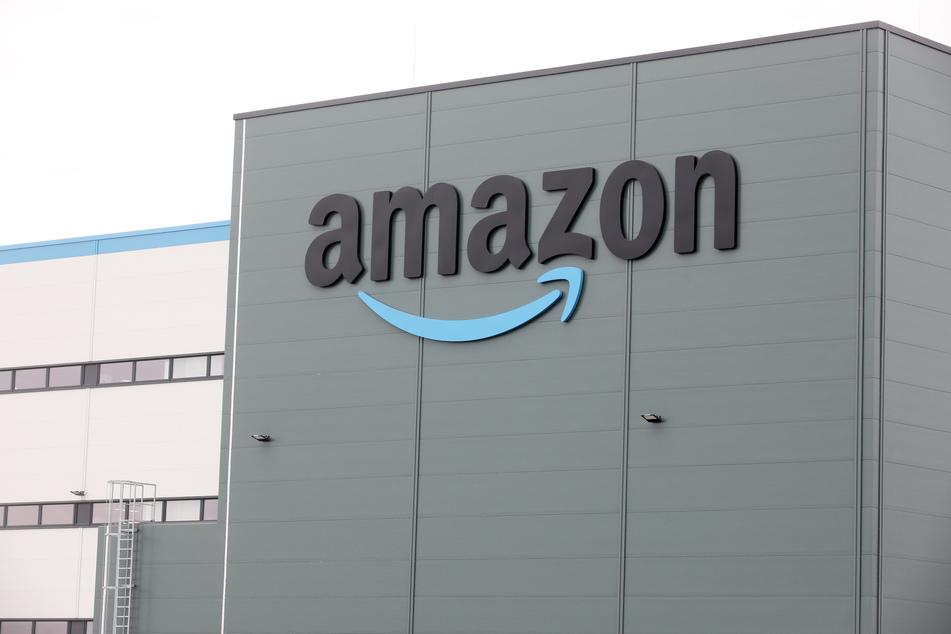Das Amazon-Logo ist an einem Logistikzentrum zu sehen. Am Standort Bad Oldesloe gab es nun eine große Razzia. (Symbolbild)