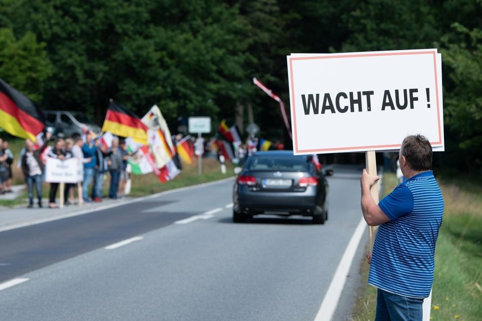"""Sachsen, Oppach: Teilnehmer eines Protests stehen mit Fahnen an der Bundesstraße 96. Ein Teilnehmer hält ein Schild mit der Aufschrift """"Wacht auf!"""". (Archivbild)"""