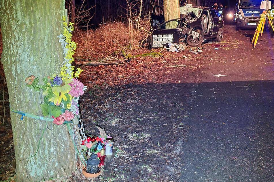Im Hintergrund ist das Wrack des VW Polo zu sehen, im Vordergrund sieht man am nächsten Baum, an dem sich vor fünf Jahren augenscheinlich ein weiterer tödlicher Verkehrsunfall ereignet hat, Blumen und Kerzen stehen.