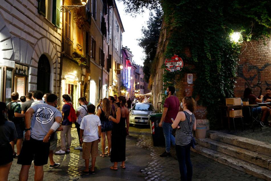 Gäste stehen mit Mundschutzen vor einem Restaurant an. Italiens Regierung bereitet nach Medienberichten eine erneute Verschärfung der Anti-Corona-Maßnahmen vor, um den steilen Anstieg der Ansteckungszahlen zu bremsen.
