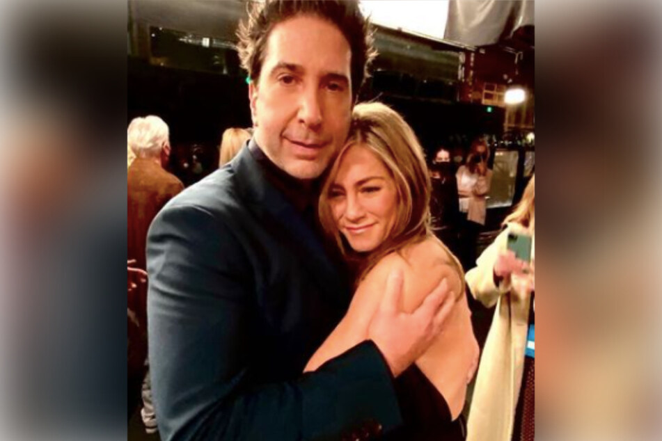 David Schwimmer (l.) hugs Jennifer Aniston (r.) after the conclusion of Friends: The Reunion in a never-before-seen photo.