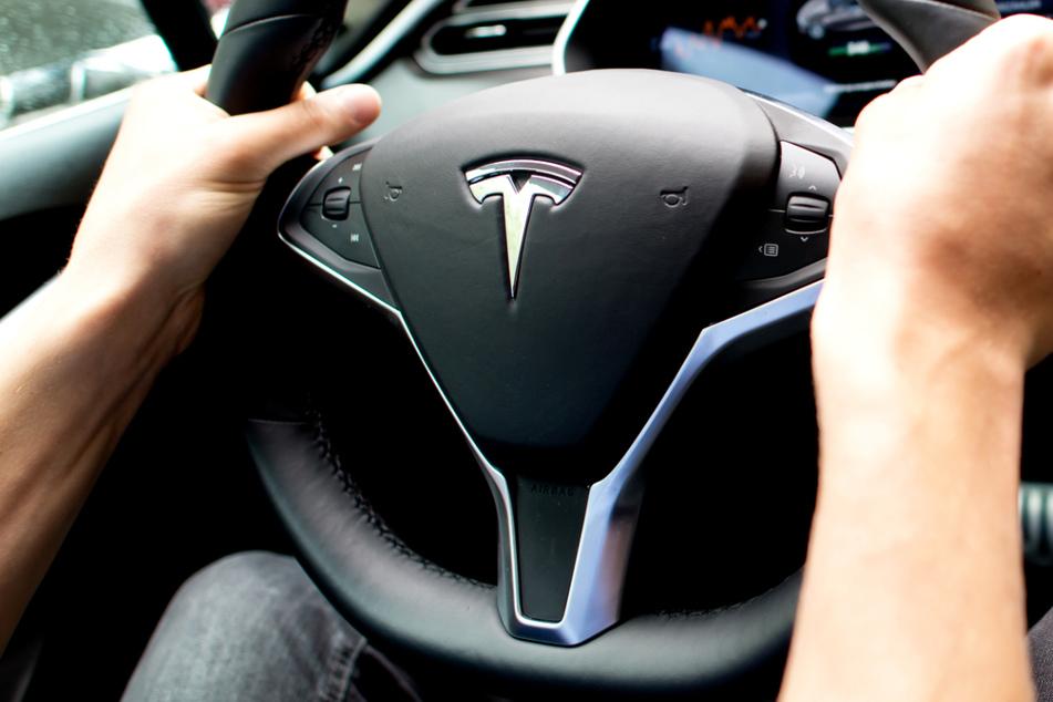 Ein Mann sitzt in einem Tesla Model S am Lenkrad.
