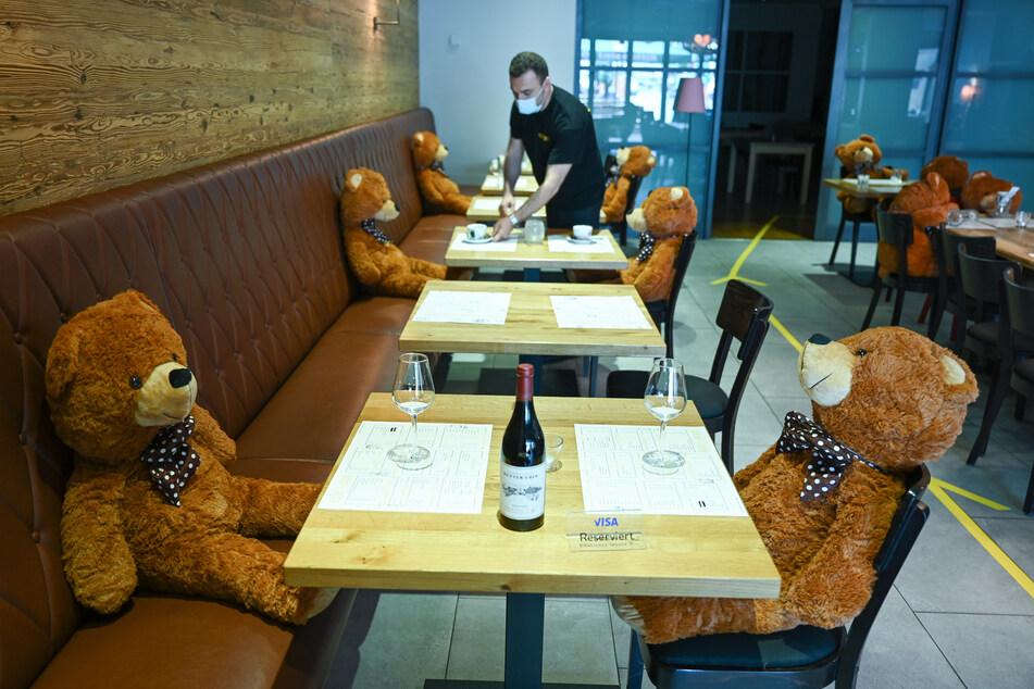 """Teddybären sitzen im Gastraum des Hofheimer Restaurants """"Beef'n Beer"""" an Tischen um den angeordneten Mindestabstand zwischen den Gästen zu gewährleisten."""