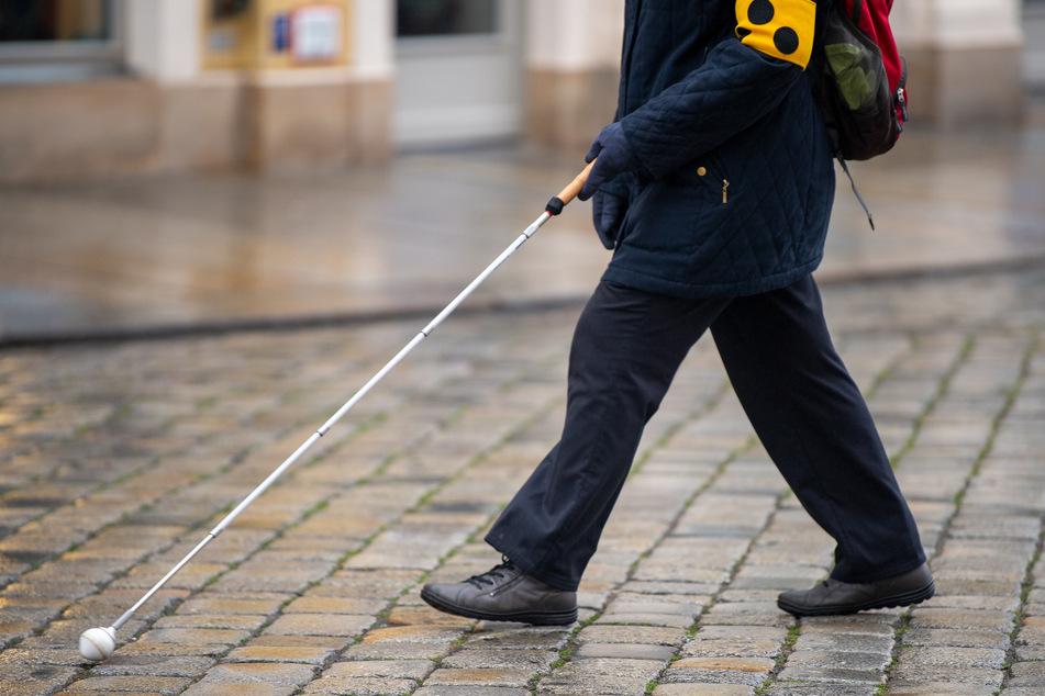 Eine Frau mit einem Blindenstock läuft über den Dresdner Neumarkt.