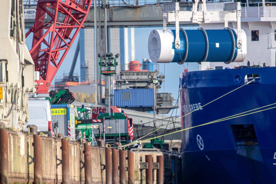 Mit einem Kran wurde am Montag der erste von sechs runden Container auf einen Waggon gehievt.