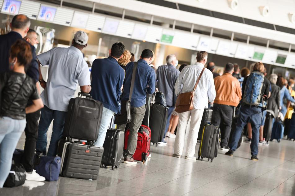 Flugreisende stehen im Terminal 1 des Frankfurter Flughafens vor einem Check-in-Schalter in einer Schlange (Symbolbild).