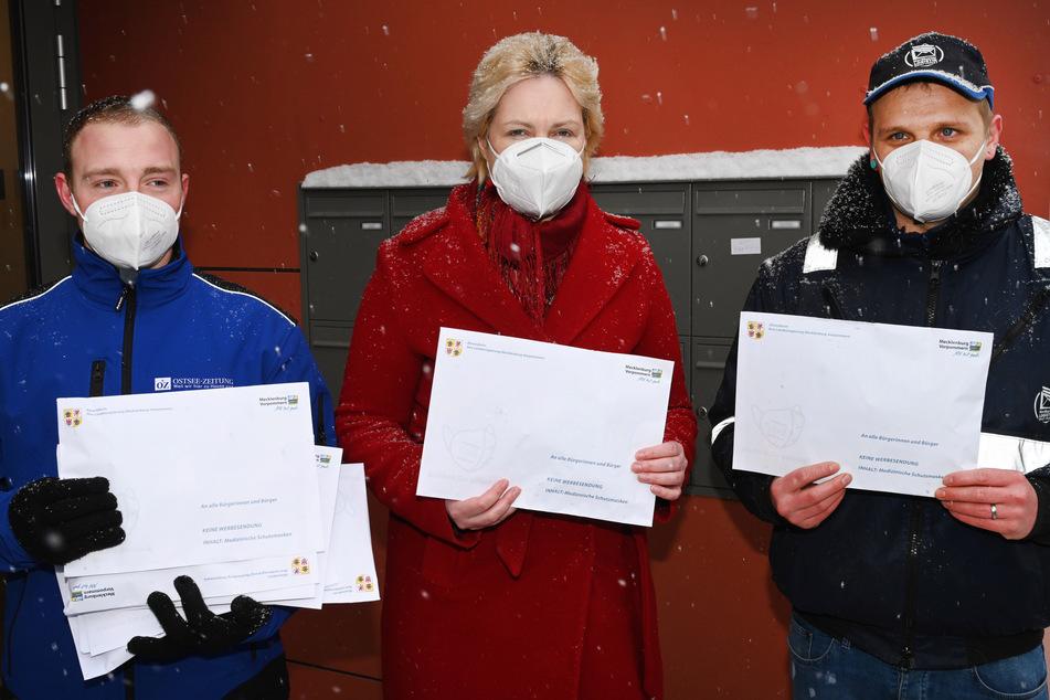 Manuela Schwesig (SPD), Ministerpräsidentin von Mecklenburg-Vorpommern, steht bei einer Verteilaktion von FFP2-Masken gemeinsam mit Philipp Wiechmann (l), Zusteller Ostsee-Zeitung, und Patrick Liefert, Zusteller Nordkurier, mit Umschlägen vor Briefkästen.