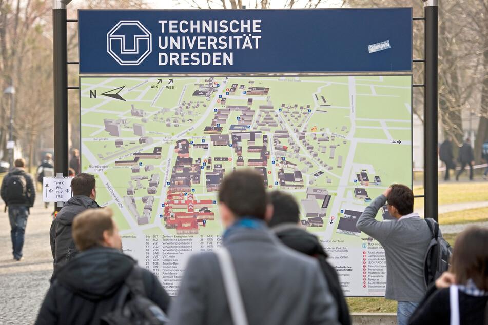 Passanten laufen an einem Gebäudeplan der Technischen Universität in Dresden vorbei.