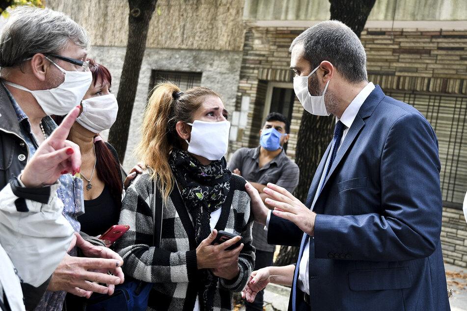 Ein Vertreter des Gesundheitswesens beruhigt Familienmitglieder von Bewohnern von einem Pflegeheim. Die ältere Menschen wurden aus dem Pflegeheim evakuiert, nachdem mehrere Bewohner der Einrichtung positiv auf das neue Coronavirus getestet wurden.