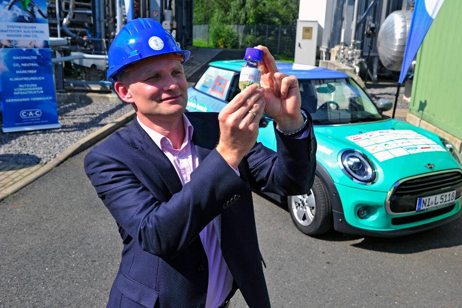 Martin Gräbner von der Professur für Energieverfahrenstechnik zeigt ein Fläschchen mit synthetischem Kraftstoff.