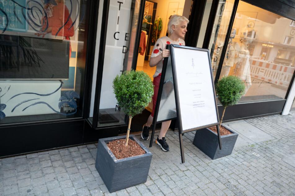 Stuttgart: Eglantina Frroku, Modedesigner und Künstlerin, trägt ein Schild aus ihrem Damendesignerbekleidungsgeschäft. Frroku öffnet ihren etwa hundert Quadratmeter großen Laden im Zuge der Lockerung der Schließungen aufgrund der Corona-Pandemie