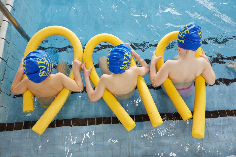 Kinder sitzen beim Schwimmunterricht im Wasser.