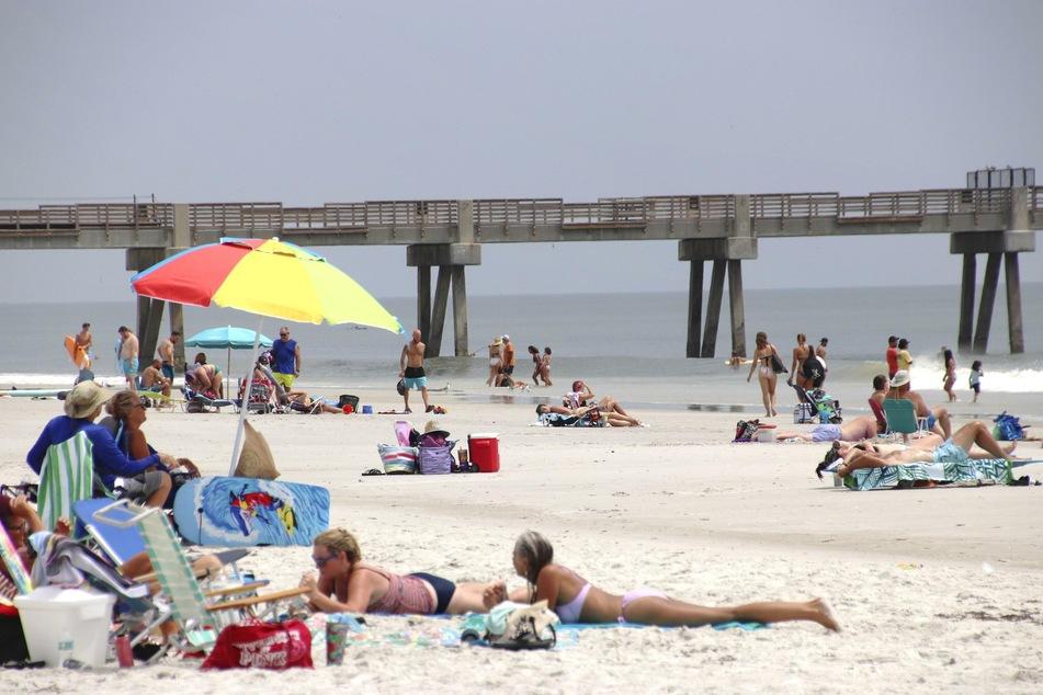 Menschen genießen das warme Wetter an einem Strand. Die Zahl der Corona-Fälle in Florida spitzt sich jedoch zu.