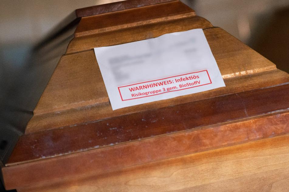 Der Sarg eines Verstorbenen wurde mit einem Warnhinweis versehen. Seit Ausbruch der Pandemie sind in Berlin 1800 Menschen am Coronavirus gestorben. (Symbolfoto)