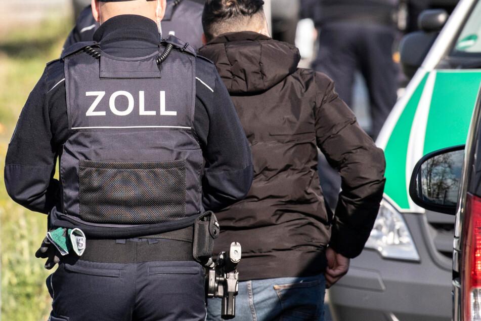 Zollbeamte führen während einer Razzia bei einem Reinigungsunternehmen in Frankfurt einen Mann zur Personalien-Überprüfung.