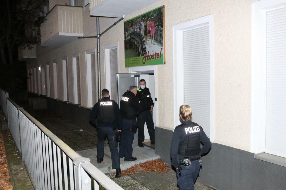 Polizeibeamte stehen im Eingangsbereich des Hostels, in dem ein illegales Bordell betrieben wurde.