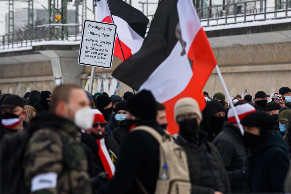 Teilnehmer der rechtsextremen Kundgebung stehen mit schwarzrotweißen Flaggen vor dem Hauptbahnhof.