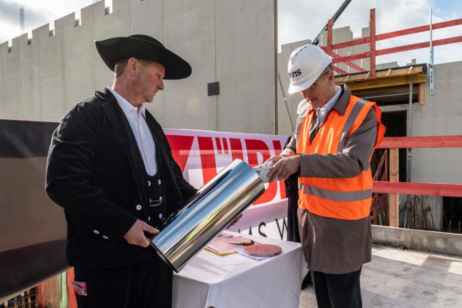 Erinnerung an den Baustart: Eins-Chef Roland Warner (56) füllte die Hülse mit Zeitdokumenten, Polier Karsten Butter (53) versenkte die Hülse im Boden.