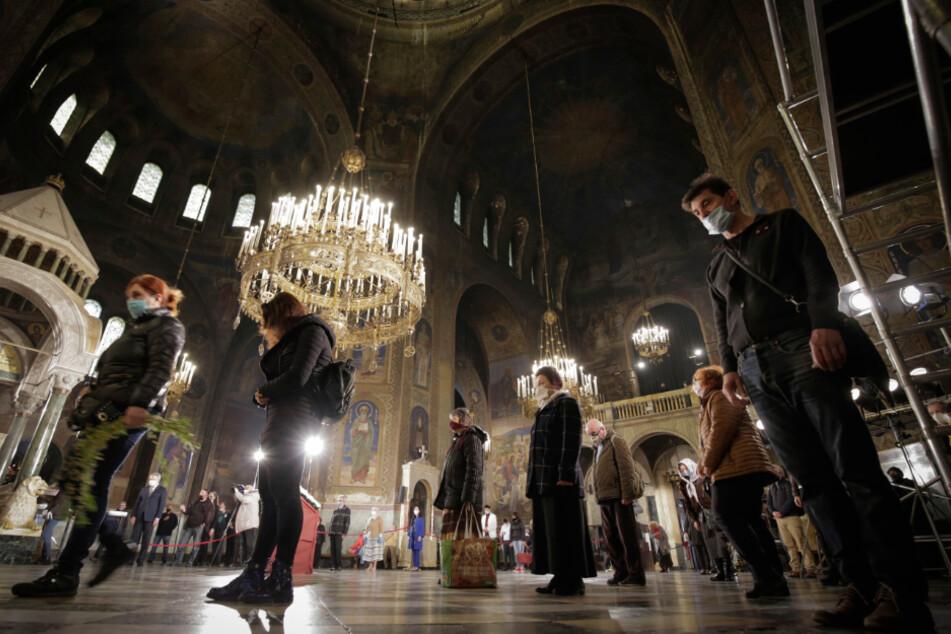 Gläubige mit Mundschutz als Maßnahme gegen das neuartige Coronavirus nehmen an einer Palmsonntagsmesse in der Alexander-Newski-Kathedrale in Bulgarien teil.