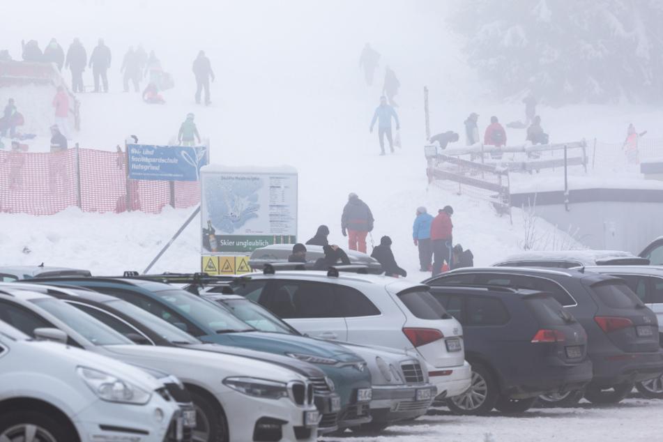 Oberried: Menschen stehen im dichten Nebel nahe dem Skilift am Haldenköpfle, während im Vordergrund der volle Parkplatz der geschlossenen Liftanlage zu sehen ist.