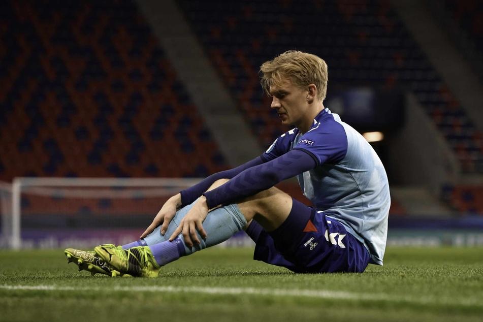 Nach dem Aus der dänischen U21 bei der EM gegen Deutschland sitzt der 22-Jährige enttäuscht am Boden.