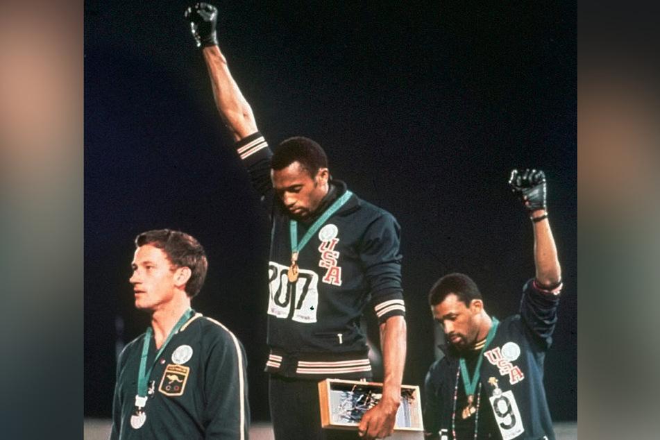 Die US-Athleten Tommie Smith (M) und John Carlos (r) strecken während der Siegerehrung bei den Olympischen Sommerspielen die Fäuste nach oben. (Archivbild)