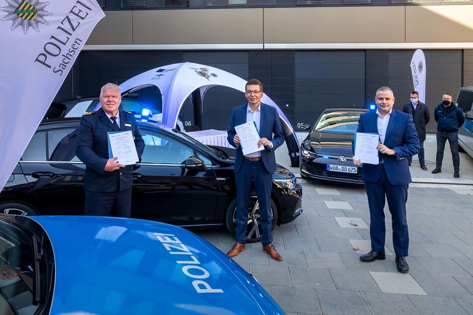 Zwei schwarze VW Golf 8 als Prototypen: (v.r.) Die VW-Führungskräfte Lars Dittert (47) und Reinhard de Vries (56) übergaben die Wagen an Landespolizeipräsident Horst Kretzschmar (61).