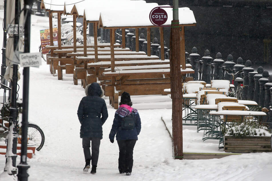 Menschen gehen bei leichtem Schneefall und Temperaturen um Minus 10 Grad Celsius im Nikolaiviertel im Bezirk Mitte an eingeschneiten Tischen und Stühlen eines Biergartens vorbei.