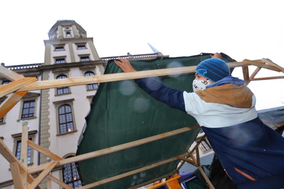 Ein Aktivist der Klimabewegung Fridays for Future errichtet einen Anbau am Protestcamp der Klimaaktivisten neben dem Rathaus.
