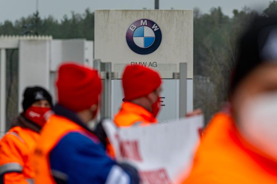Gewerkschaftsmitglieder stehen vor dem Eingang eines BMW-Werks.
