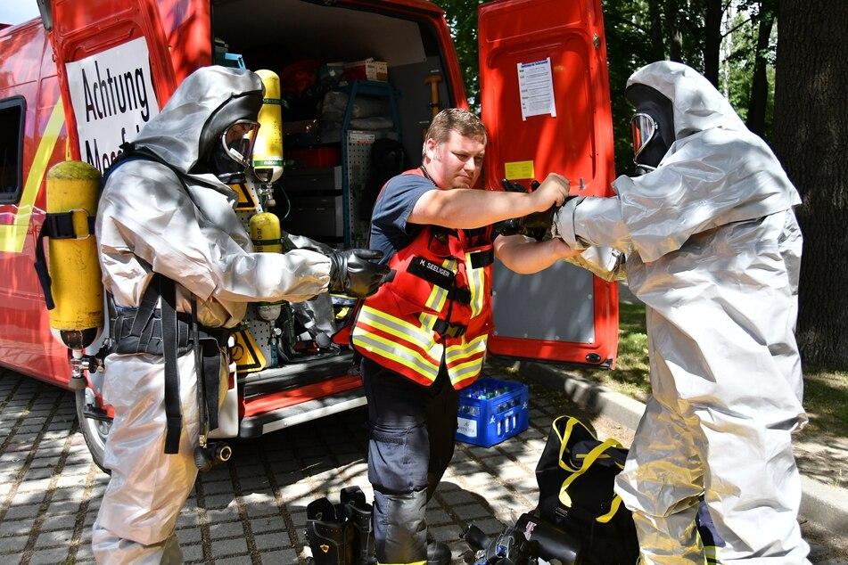 Schutz muss sein! Ein Kollege hilft den Einsatzkräften mit ihren Anzügen.